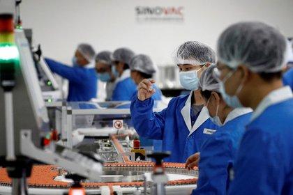 Una foto de archivo de personas que trabajan en el complejo de empaque de la compañía farmacéutica china Sinovac Biotech, que está desarrollando una vacuna experimental contra el coronavirus, durante una visita de prensa del gobierno en Beijing, China.  24 de septiembre de 2020 (Reuters) / Thomas Peter / Archivo