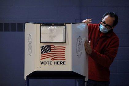 Un hombre esteriliza una máquina de votación a principios de Nueva York (Reuters / Andrew Kelly)