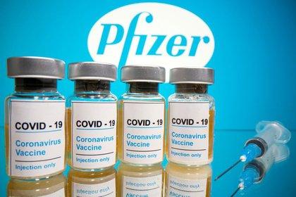 Frascos y jeringa frente al logotipo de Pfizer
